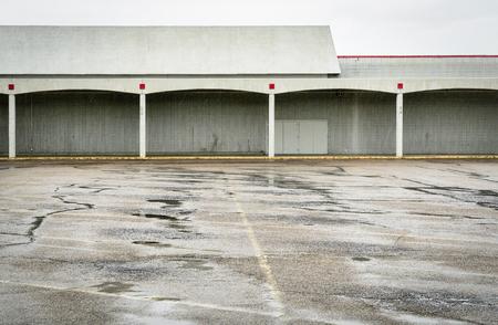 Regen over leeg parkeerterrein van een gesloten winkelcomplex Stockfoto