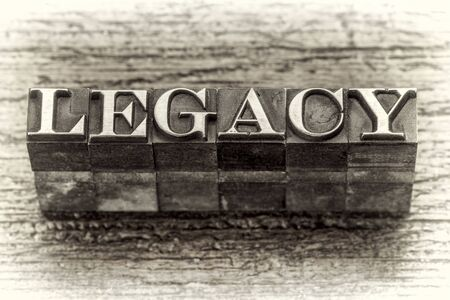 white achievement: legacy  word in mixed vintage metal type printing blocks over grunge wood, black and white image