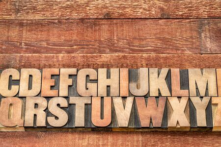 letterpress words: alphabet abstract in vintage letterpress printing blocks against rustic red painted barn wood with a copy space