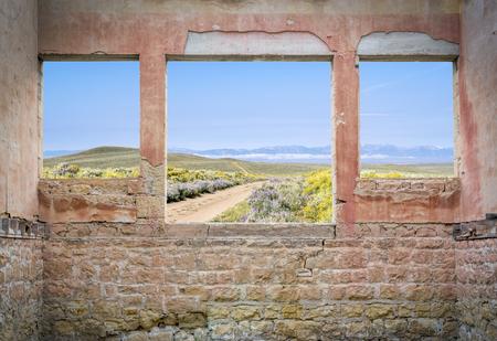 ranch road through mountain valley as seen through windows of an abandoned house Stock Photo