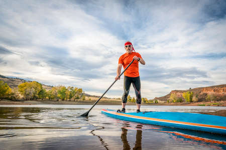 A senior male paddling a stand up paddleboard on a calm mountain lake - Horsetooth Reservoir near Fort Collins, Colorado, fall scenery