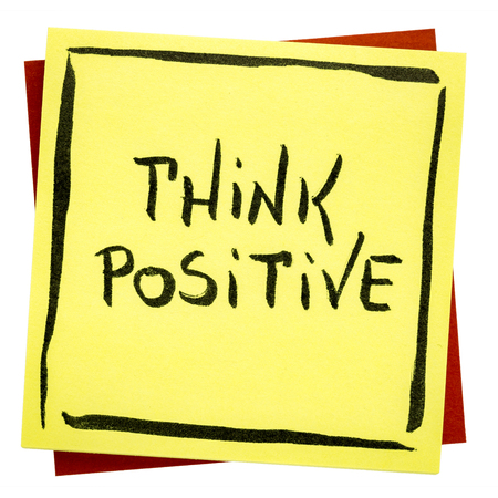 Think positive inspirational reminder - handwriting on an isolated sticky note Banco de Imagens