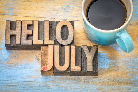 Hello July - word abstract in vintage letterpress wood type blocks against grunge wooden background with a cup of coffee