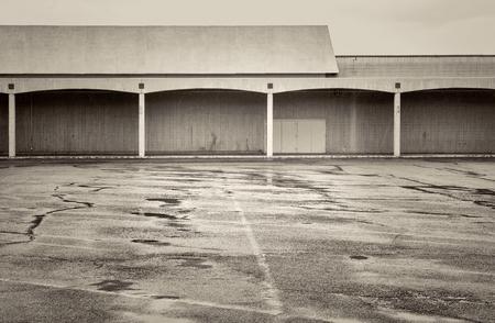 Rain over empty parking lot of a shut down mall, black and white platinum toned image, 版權商用圖片