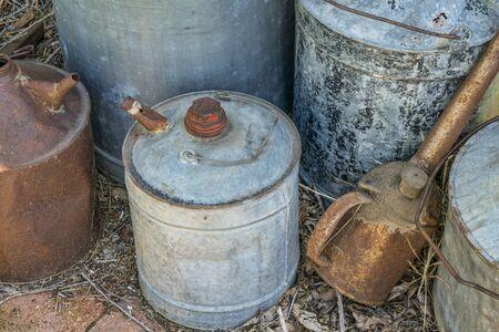 ファームのワーク ショップで無視されるさまざまなサイズのヴィンテージのさびたオイル缶