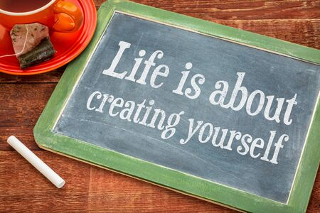 Life is about creating yourself  - motivational text on a slate blackboard with chalk and cup of tea Stock Photo