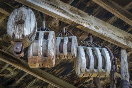 vintage wooden pulleys in an old barn or workshop Stock Photo
