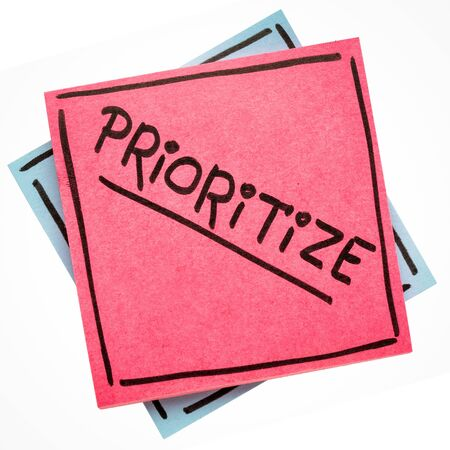 prioritize advice or reminder - handwriting on an isolated sticky note Stock Photo
