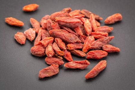 chinese wolfberry: a heap of dried Tibetan goji berries (wolfberry) on a dark ceramic  surface