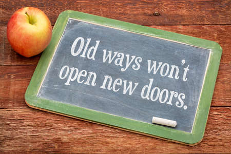 not open: Old ways do not open new doors - motivational quote on a slate blackboard against red barn wood