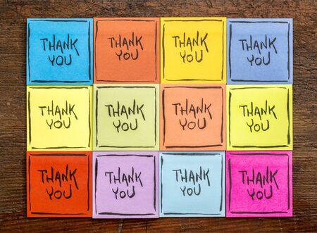thank you abstract - handwriting on a set of colorful sticky notes against rustic wood
