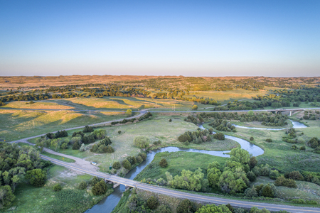 sandhills: aerial view of a highway and bridge over the Dismal River in Nebraska Sandhills near Thedford, spring scenery lit by sunrise light