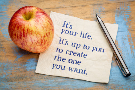 Its your life. Its up to you to create the one you want. Motivational handwriting on a napkin with a fresh apple