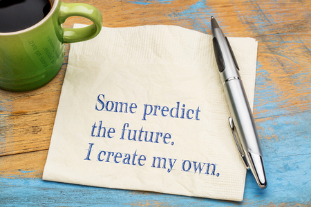Some predict the future. I create my own. Motivational handwriting on a napkin with a cup of coffee