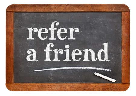 refer a friend  - white chalk text on a vintage slate blackboard