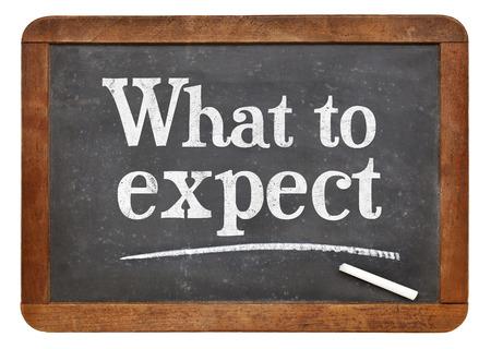 Wat te verwachten - wit krijt tekst op een vintage leisteen schoolbord Stockfoto