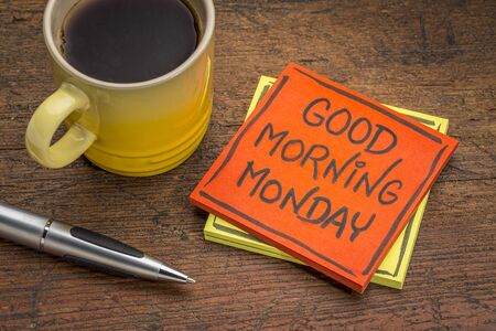 Good morning Monday - cheerful message on a sticky note with a cup of coffee and pen