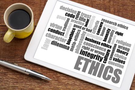 Ethiek en morele dilemma woordwolk op een digitale tablet met een kopje koffie