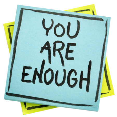 you are  enough inspirational concept - handwriting in black ink on an isolated sticky note