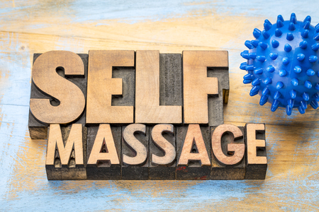self massage word in letterpress wood type with a spiky rubber  ball Stock Photo