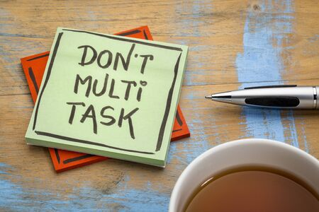 do not multitask -  efficiency advice on a sticky note with a cup of tea