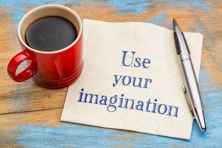 Use your imagination reminder or advice - handwriting on a napkin with a cup of coffee