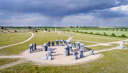 ALLIANCE, NE, USA - July 9, 2017:  Carhenge - famous car sculpture  created by Jim Reinders, a modern replica of  Englands Stonehenge using old cars., aerial view with a storm in background Editorial
