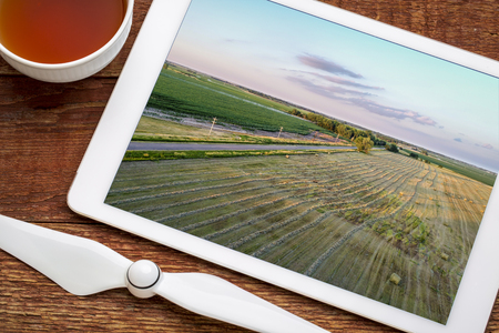 aerial view of rural Nebraska landscape with a narrow road, meadow and corn field, reviewing image on a digital tablet