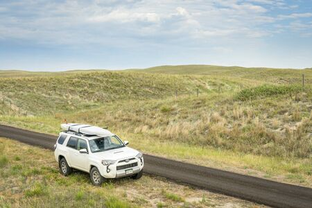 sandhills: SENECA, NE, JULY 7, 2017: Toyota 4Runner SUV (2016 Trail edition) carrying  a stand up paddleboard on a narrow back country road in Nebraska Sandhills