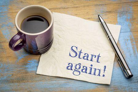 Beginn opnieuw motiverende herinnering of advies - handschrift op een servet met een kop van espresso