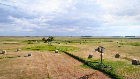 干し草俵とネブラスカ Sandhills の風車-空撮 写真素材