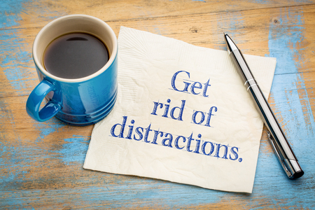 Get rid of distractions advice or reminder - handwriting on a napkin with a cup of espresso coffee Standard-Bild