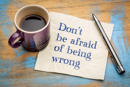 Wees niet bang om ongelijk te hebben - inspirerend handschrift op een servet met een kopje espresso