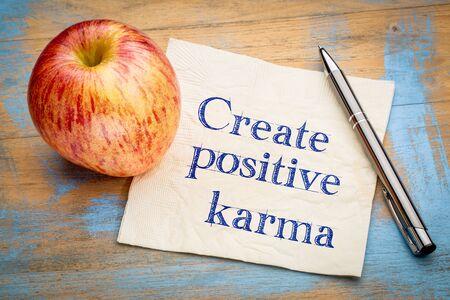 create positive karma - motivational handwriting on a napkin with  apple