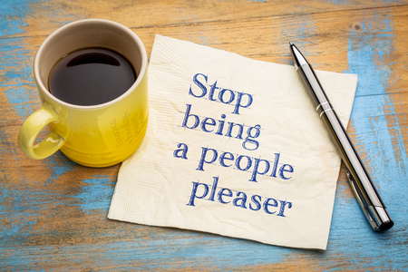 Stop being a people pleaser - handwriting on a napkin with a cup of espresso coffee 스톡 콘텐츠