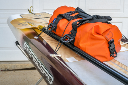 Fort Collins, CO, USA - August 1, 2017: Preparing for a paddling expedition in a driveway - waterproof duffel and Werner paddle on a stern deck of the Starboard Expedition paddleboard.