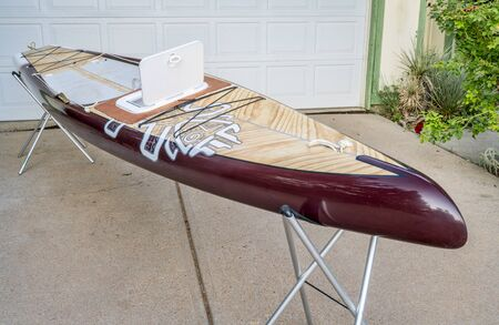 Fort Collins, CO, USA - August 1, 2017: Preparing for a paddling expedition in a driveway - Starboard Expedition paddleboard with a home made hatch to storage compartment.