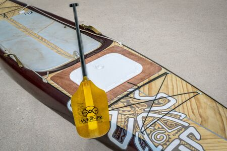 starboard: Fort Collins, CO, USA - July 29, 2017: Preparing for a paddling expedition in a driveway - Starboard Expedition paddleboard with a custom made hatch to storage compartment and a paddle.