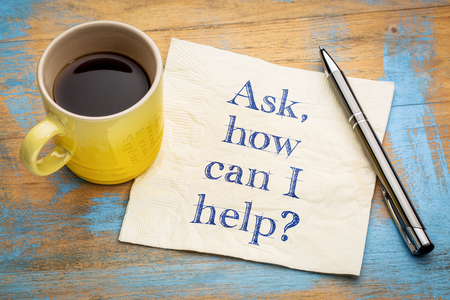 Ask, how can I help? - handwriting on a napkin with a cup of espresso coffee