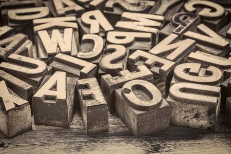 background of random vintage letterpress printing blocks on a grunge rustic wood, sepia toned image