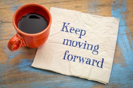 Keep moving forward reminder or advice - handwriting on a napkin with a cup of espresso coffee