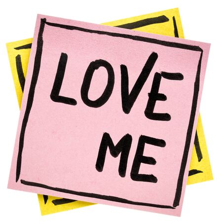 Love me reminder note - handwriting in black ink on an isolated sticky note