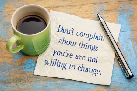 Do not complain about things you are not willing to change - handwriting on a napkin with a cup of espresso coffee
