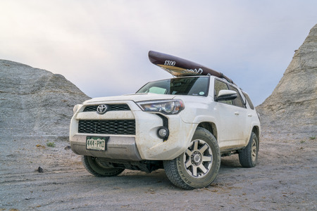 Castle Rock, KS, USA - August 14, 2017:  Toyota 4Runner SUV (2016 Trail edition) carrying  a stand up paddleboard  is driving through badlands and prairie of Kansas. Redakční
