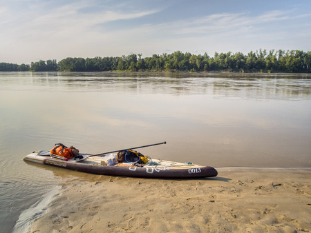 Dundee, MO, USA - August 10, 2017 - Stand up paddleboard (Starboard Expedition SUP) at rest stop during Missouri RIver 340 race, ultra marathon paddling race from Kansas City to St Charles.