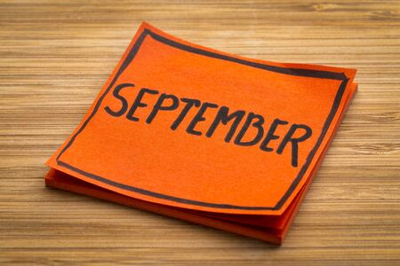 September reminder - handwriting on a sticky note against bamboo wood board
