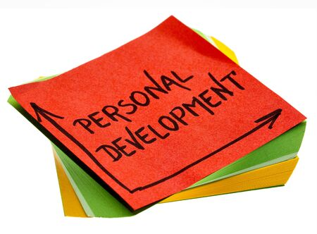 personal development - handwriting in a black ink on isolated sticky note Banco de Imagens