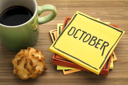 Oktoberherinnering - handschrift in zwarte inkt op een kleverige nota met een kop koffie en een koekje Stockfoto