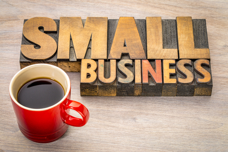 small business word abstract in vintage letterpress wood type with a cup of coffee