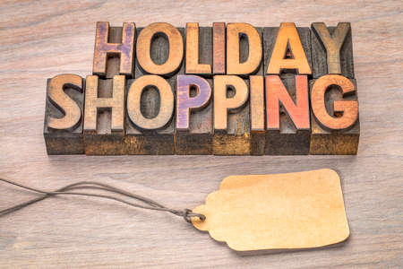 holiday shopping word abstract in vintage letterpress wood type with a blank price tag